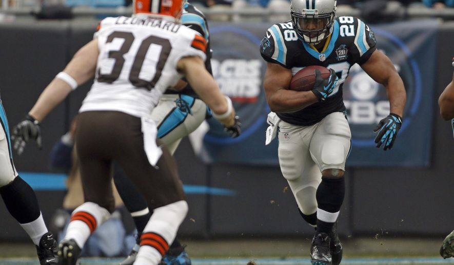 Carolina Panthers' Jonathan Stewart (28) runs as Cleveland Browns' Jim Leonhard (30) defends in the first half of an NFL football game in Charlotte, N.C., Sunday, Dec. 21, 2014. (AP Photo/Bob Leverone)