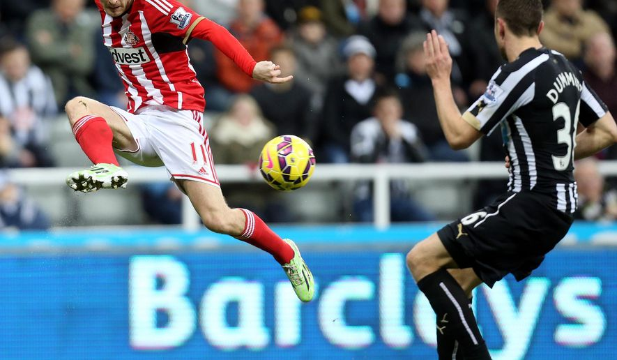 Sunderland's Adam Johnson, left, vies for the ball with Newcastle United's Paul Dummett, right, during their English Premier League soccer match at St James' Park, Newcastle, England, Sunday, Dec. 21, 2014. (AP Photo/Scott Heppell)