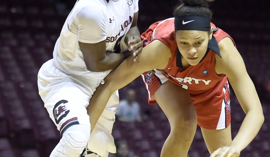 South Carolina guard Khadijah Sessions, left, and Liberty forward Mickayla Sanders go after a loose ball during the first half of an NCAA college basketball game Sunday, Dec. 21, 2014, in Minneapolis. (AP Photo/Hannah Foslien)