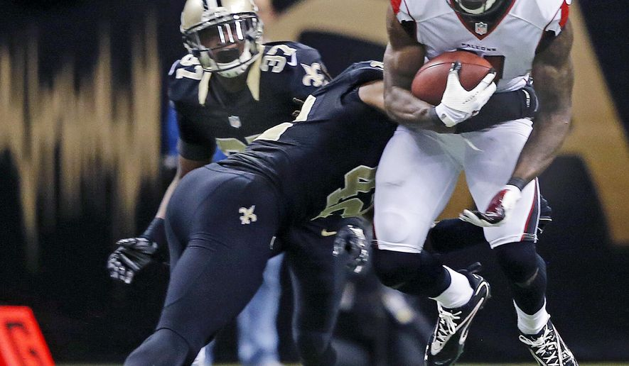 Atlanta Falcons wide receiver Julio Jones (11) is tackled by New Orleans Saints defensive back Pierre Warren (42) in the second half of an NFL football game in New Orleans, Sunday, Dec. 21, 2014. (AP Photo/Bill Haber)