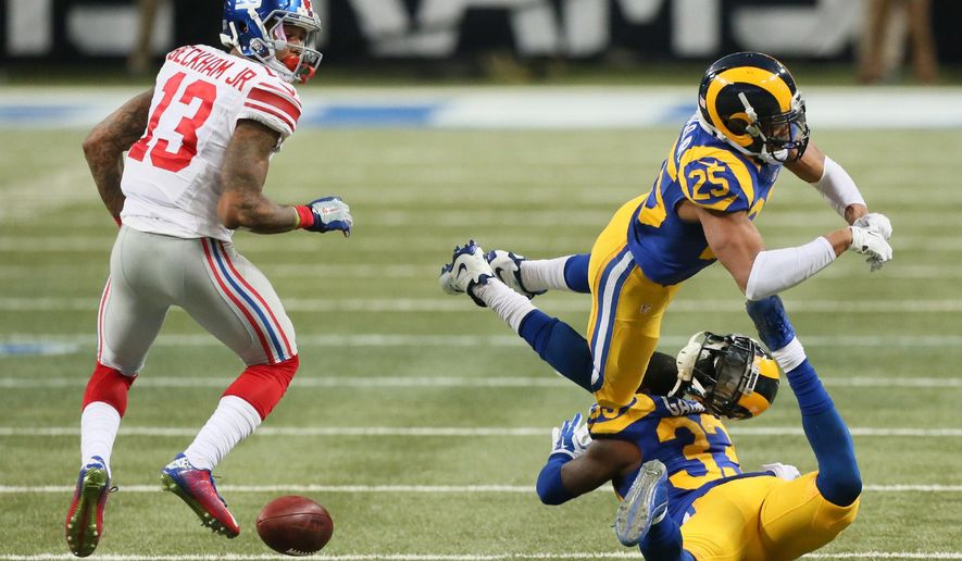 St. Louis Rams safety T.J. McDonald (25) knocks the helmet off teammate E.J Gaines as they collide while trying to intercept a pass in third quarter action duringthe NFL football game on Sunday, Dec. 21, 2014, at the Edward Jones Dome in St. Louis.  Gaines was taken off the field on a cart.  At left is New York Giants wide receiver Odell Beckham Jr. (AP Photo/St. Louis Post-Dispatch, Chris Lee)  EDWARDSVILLE INTELLIGENCER OUT; THE ALTON TELEGRAPH OUT
