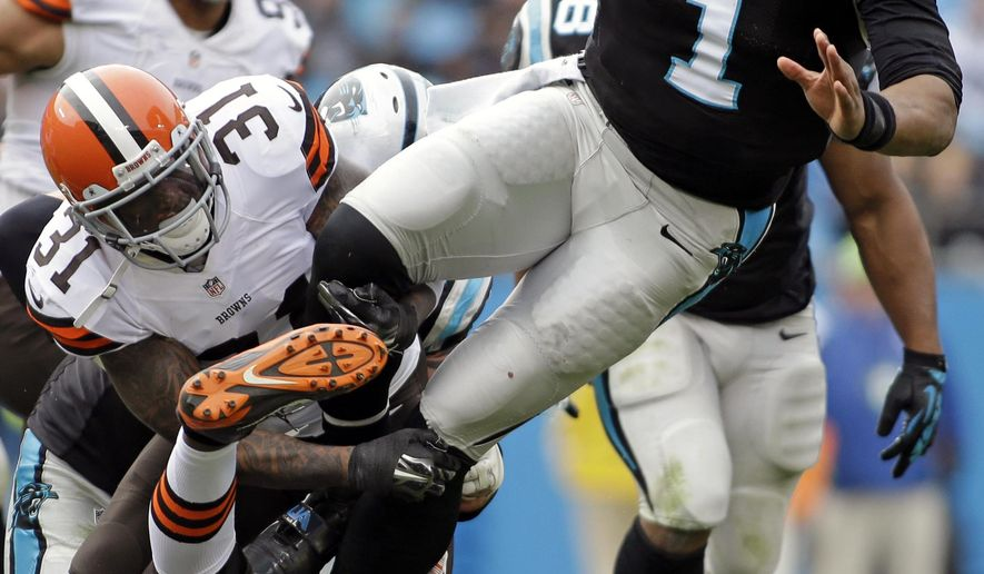 Carolina Panthers' Cam Newton (1) is tackled by Cleveland Browns' Donte Whitner (31) and Pierre Desir (26) in the first half of an NFL football game in Charlotte, N.C., Sunday, Dec. 21, 2014. (AP Photo/Bob Leverone)