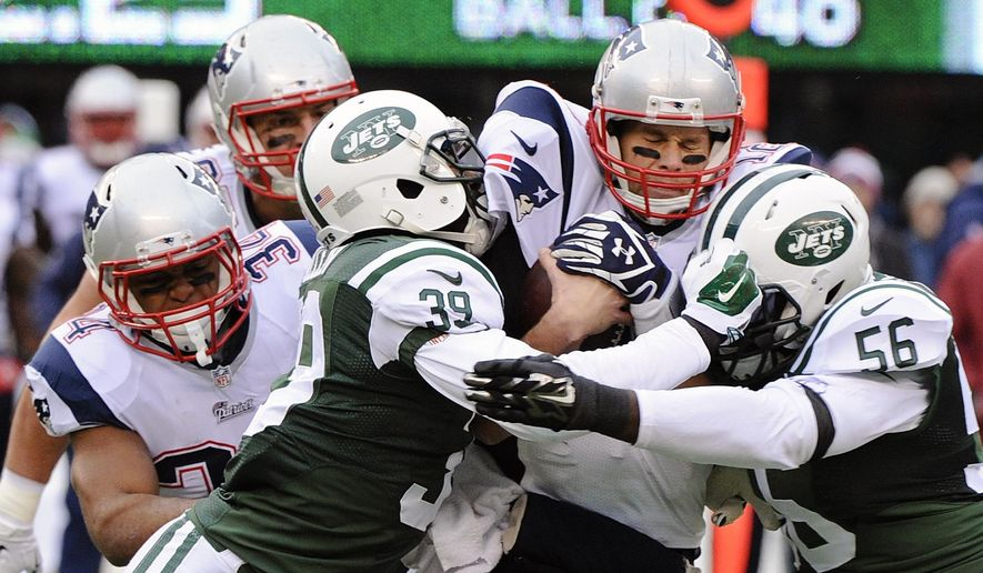 New York Jets cornerback Antonio Allen (39) and Demario Davis (56) sack New England Patriots' Tom Brady, second from right, during the first half of an NFL football game Sunday, Dec. 21, 2014, in East Rutherford, N.J. (AP Photo/Bill Kostroun)