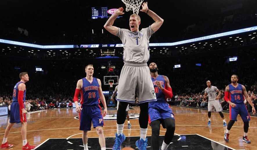 Brooklyn Nets' Mason Plumlee (1) reacts after scoring ahead of Detroit Pistons' Kyle Singer (25) and Andre Drummond (0) during the second quarter of an NBA basketball game Sunday, Dec. 21, 2014, in New York. Brooklyn won 110-105. (AP Photo/Jason DeCrow)