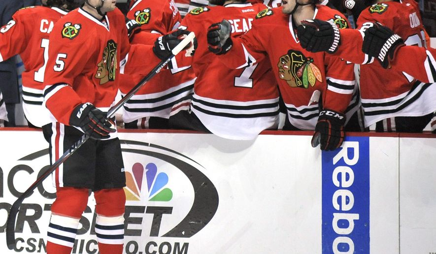CORRECTS NAME OF TORONTO TEAM TO MAPLE LEAFS - Chicago Blackhawks' David Rundblad (5), of Sweden, celebrates with teammates on the bench during the first period of an NHL hockey game against the Toronto Maple Leafs in Chicago, Sunday, Dec. 21, 2014. (AP Photo/Paul Beaty)