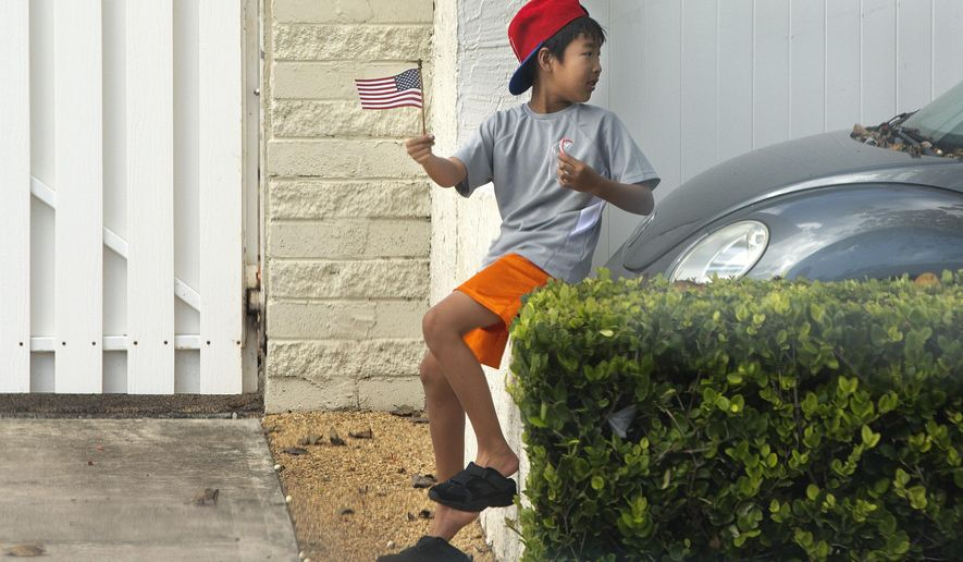 A boy holding a U.S. flag and a candy cane looks for the arrival of the motorcade carrying President Barack Obama to play golf at Marine Corps Base Hawaii, in Kailua, Hawaii, Saturday, Dec. 20, 2014. (AP Photo/Jacquelyn Martin)