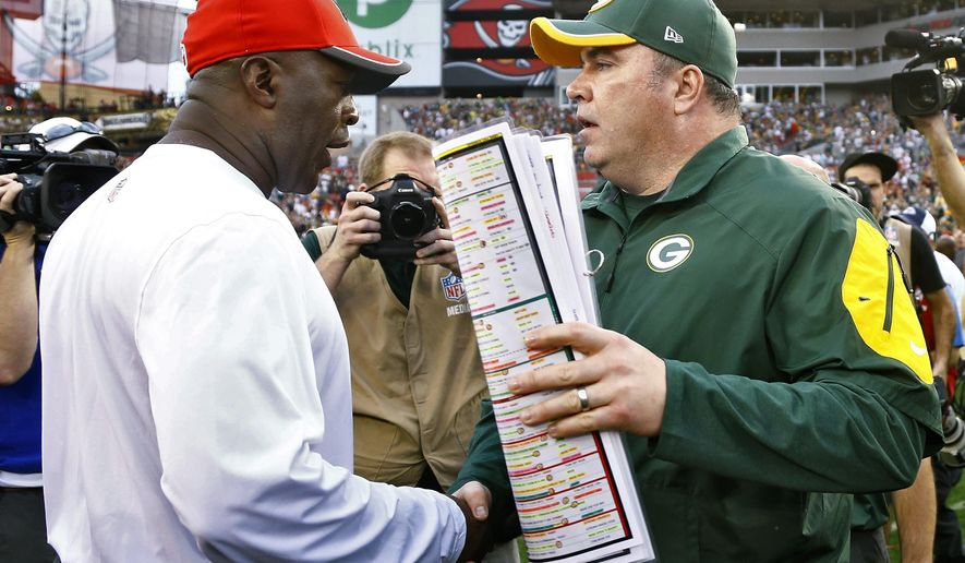 Green Bay Packers head coach Mike McCarthy, right, shakes hands with Tampa Bay Buccaneers head coach Lovie Smith after the Packers defeated the Buccaneers 20-3 during an NFL football game Sunday, Dec. 21, 2014, in Tampa, Fla. (AP Photo/Brian Blanco)