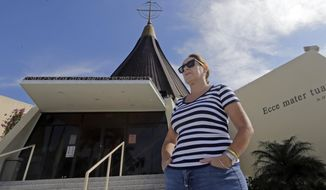 In this photo taken Thursday, Dec. 18, 2014, Larisa Alonso talks to a reporter at Our Lady of Charity Catholic church in Miami. Many Catholics have expressed pride in seeing Francis stirring hopes of progress in communist Cuba, but some Cuban-Americans say their spiritual leader betrayed them (AP Photo/Alan Diaz)