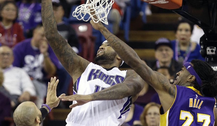 Sacramento Kings center DeMarcus Cousins, center, goes to the basket between Los Angeles Lakers' Carlos Boozer, left, and Jordan Hill during the first half of an NBA basketball game in Sacramento, Calif., Sunday, Dec. 21, 2014.(AP Photo/Rich Pedroncelli)