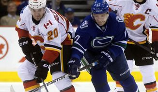 Calgary Flames' Curtis Glencross, left, and Vancouver Canucks' Radim Vrbata, of the Czech Republic, battle for the puck during the first period of an NHL hockey game in Vancouver, British Columbia, on Saturday, Dec. 20, 2014. (AP Photo/The Canadian Press, Darryl Dyck)