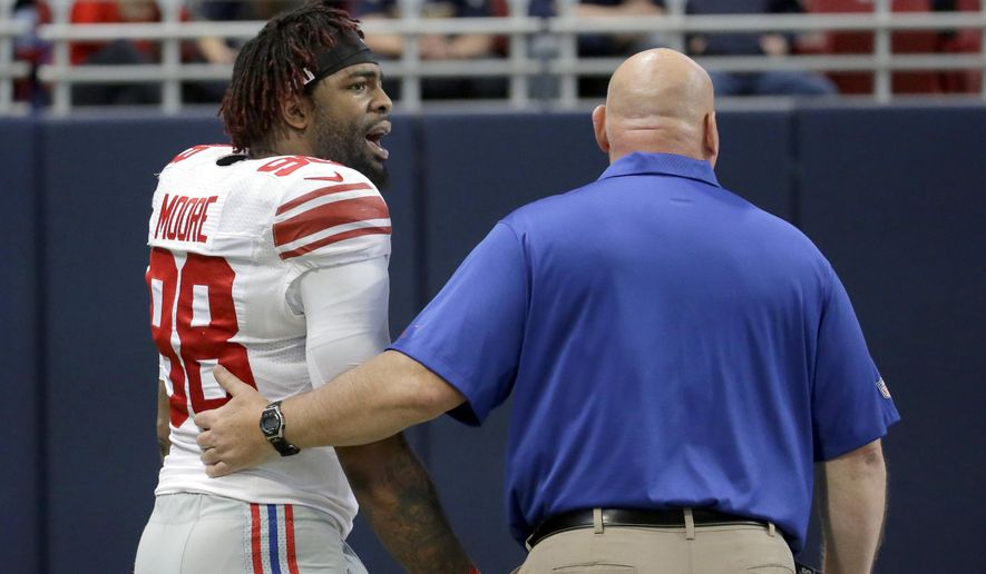 New York Giants defensive end Damontre Moore, left, walks off the field after being ejected during the first half of an NFL football game against the St. Louis Rams, Sunday, Dec. 21, 2014, in St. Louis. (AP Photo/Charlie Riedel)