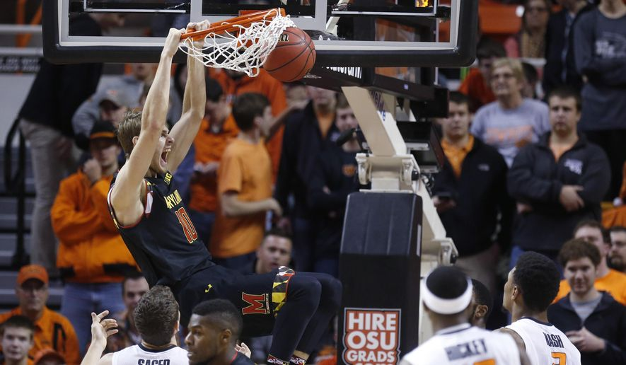 Maryland's Jake Layman (10) yells as he dunks in front of Oklahoma State's Christien Sager (15), Anthony Hickey Jr. (12) and Le'Bryan Nash (2) in the first half of an NCAA college basketball game in Stillwater, Okla., Sunday, Dec. 21, 2014. (AP Photo/Sue Ogrocki)