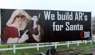 This Dec. 20, 2014 still frame from video by KHSL/KNVN-TV shows a billboard showing Santa Claus holding an assault rifle, posted by the Down Range indoor training facility in Chico, Calif. The gun range owners told Action News Now they didn't intend to make the ad offensive. They said some people give guns as Christmas presents, and they put the ad up along a highway on the outskirts of town to draw attention to their fledgling business. (AP Photo/KHSL/KNVN-TV)