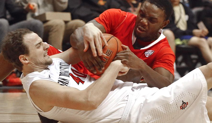 Ball State guard Francis Kiapway, right, and San Diego State forward Matt Shrigley battle for a loose ball during the first half of an NCAA college basketball game  Saturday, Dec. 20, 2014, in San Diego. (AP Photo/Lenny Ignelzi)