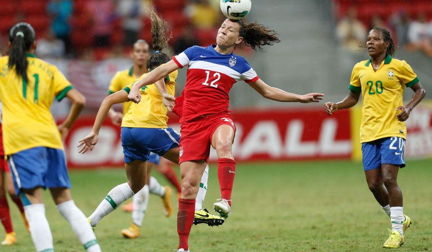 United States' Lauren Holiday, center, (12) heads the ball during a final match of the International Women's Football Tournament at the National Stadium in Brasilia, Brazil, Sunday, Dec. 21, 2014. (AP Photo/Eraldo Peres)