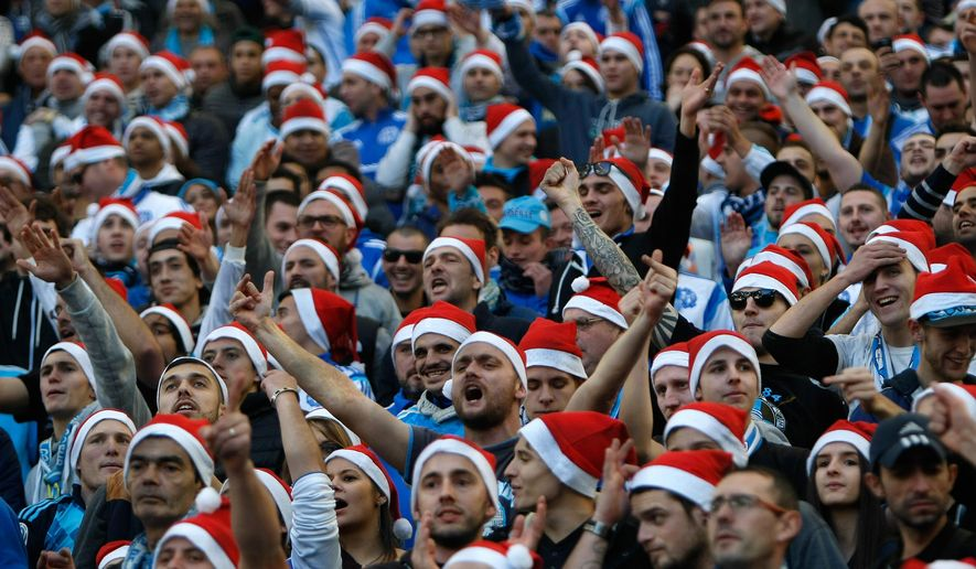 Marseille supporters wearing Santa Claus  hats, shout slogans, during the League One soccer match between Marseille and Lille, at the Velodrome Stadium, in Marseille, southern France, Sunday,  Dec. 21, 2014. (AP Photo/Claude Paris)