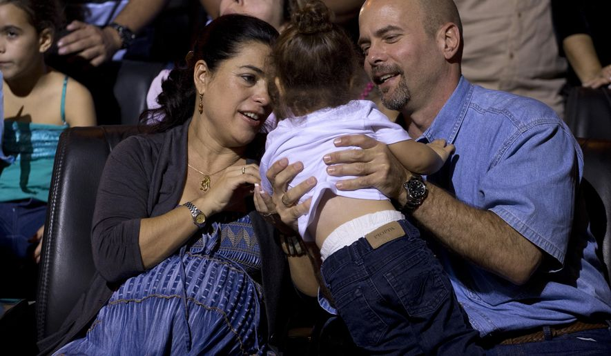 """Gerardo Hernandez, right, member of """"The Cuban Five,"""" and his wife Adriana Perez, raise in their arms a little girl during a concert of singer Silvio Rodriguez in Havana, Cuba, Saturday, Dec. 20, 2014. Hernandez flew back to their homeland on Wednesday in a quiet exchange of imprisoned spies, part of a historic agreement to restore relations between the two long-hostile countries. (AP Photo/Ramon Espinosa)"""