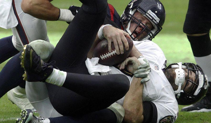 Houston Texans defensive end J.J. Watt (99) sacks Baltimore Ravens quarterback Joe Flacco (5) during the second half of an NFL football game Sunday, Dec. 21, 2014, in Houston. (AP Photo/Patric Schneider)