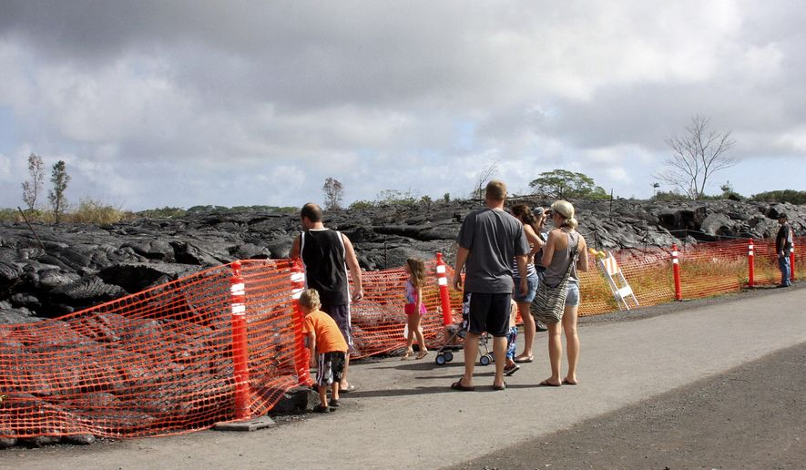 Visitors view a section of cooled lava from lava flow that began on June 27 as it approaches a shopping center in Pahoa, Hawaii, Friday, Dec. 19, 2014. Lava flowing in a rural Hawaii town continues to slow down and is estimated to reach a shopping center in about eight days. (AP Photo/Tim Wright)
