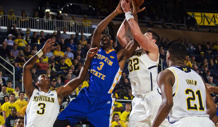 Coppin State forward Arnold Fripp (3) fights for a rebound with Michigan forward Ricky Doyle (32), with guard Kameron Chatman (3) and guard Zak Irvin (21) watching, in the first half of an NCAA college basketball game at Crisler Center in Ann Arbor, Mich., Monday, Dec. 22, 2014. (AP Photo/Tony Ding)