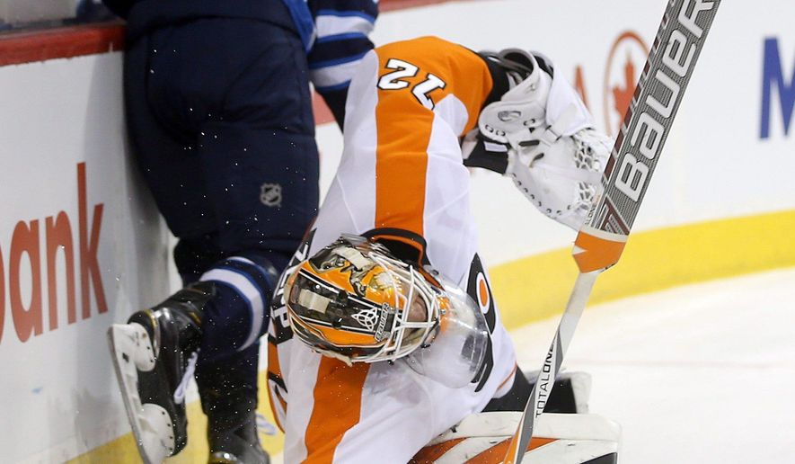 Winnipeg Jets' Michael Frolik (67) collides with Philadelphia Flyers goaltender Rob Zepp (72) during the second period of an NHL hockey game, Sunday, Dec. 21, 2014 in Winnipeg, Manitoba. (AP Photo/The Canadian Press, Trevor Hagan)