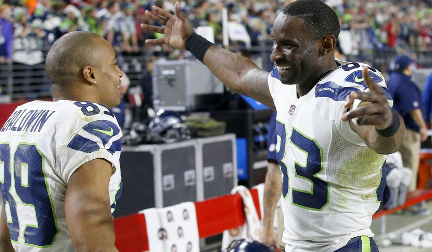 Seattle Seahawks' Ricardo Lockette (83) smiles as he hugs Doug Baldwin (89) in celebration on the team bench in the closing moments of an NFL football game against the Arizona Cardinals Sunday, Dec. 21, 2014, in Glendale, Ariz.  The Seahawks defeated the Cardinals 35-6. (AP Photo/Ross D. Franklin)
