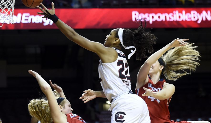 South Carolina forward A'ja Wilson (22) shoots over Liberty center Ashley Rininger, left, and forward Catherine Kearney (44) of an NCAA college basketball game Sunday, Dec. 21, 2014, in Minneapolis. South Carolina won 84-44. (AP Photo/Hannah Foslien)