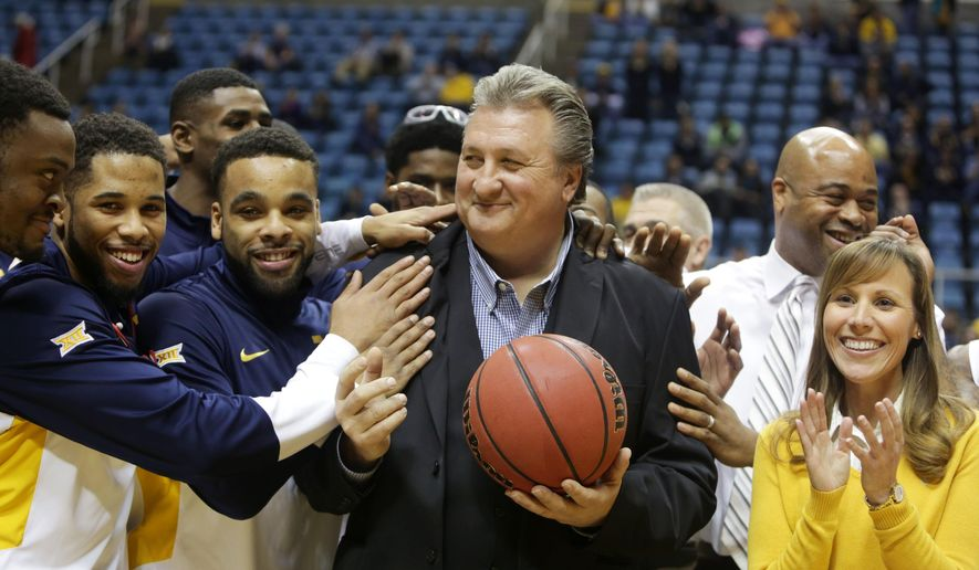 West Virginia head coach Bob Huggins celebrates his 750th career victory during an NCAA college basketball game, Monday, Dec. 22, 2014, in Morgantown, W.Va. West Virginia defeated Wofford 77-44. (AP Photo/Raymond Thompson)