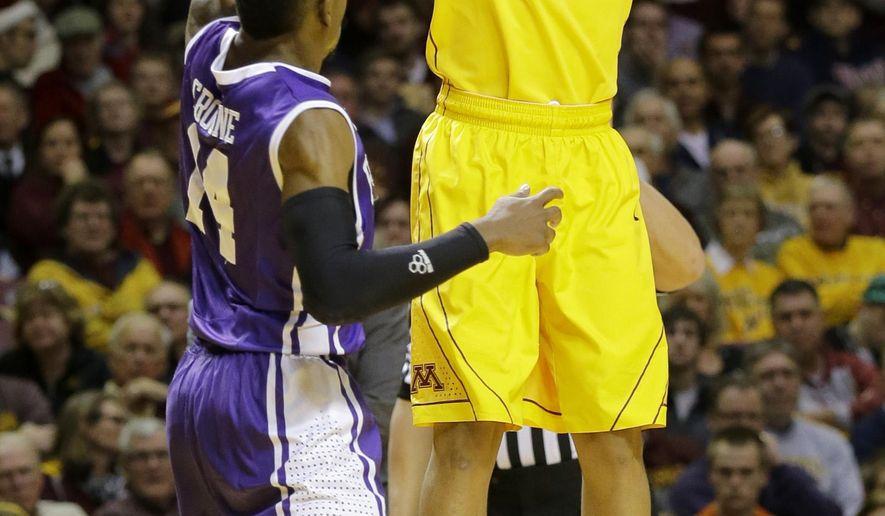 Minnesota guard Nate Mason (2) shoots over Furman guard Stephen Croone (14) during the second half of an NCAA college basketball game in Minneapolis, Monday, Dec. 22, 2014. Minnesota won 86-76. (AP Photo/Ann Heisenfelt)