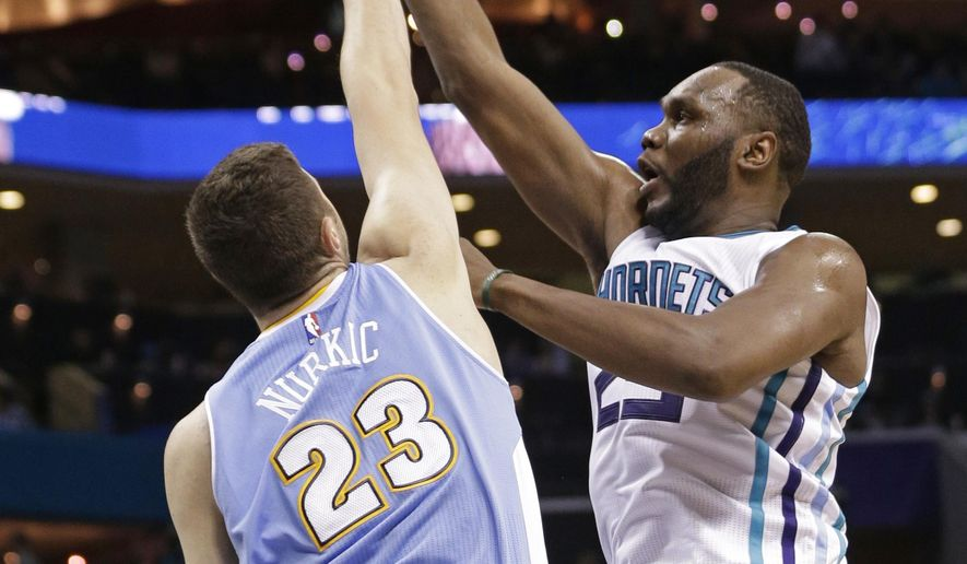 Charlotte Hornets' Al Jefferson, right, shoots over Denver Nuggets' Jusuf Nurkic during the first half of an NBA basketball game in Charlotte, N.C., Monday, Dec. 22, 2014. (AP Photo/Chuck Burton)