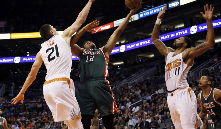 FILE - In this Dec. 15, 2014, file photo, Milwaukee Bucks' Jabari Parker (12) shoots between Phoenix Suns' Alex Len (21) and Markieff Morris (11) during the first half of an NBA basketball game, in Phoenix. The Bucks have made it out of the first round of the playoffs one time in the last 25 years, play in a dinosaur of an arena and in need of fresh ideas to breathe some energy into them. General manager John Hammond, new coach Jason Kidd and a promising young roster featuring Giannis Antetokounmpo and Parker have pushed the team to a 14-14 record, just one win away from the victory total for all of last season. (AP Photo/Matt York, File)