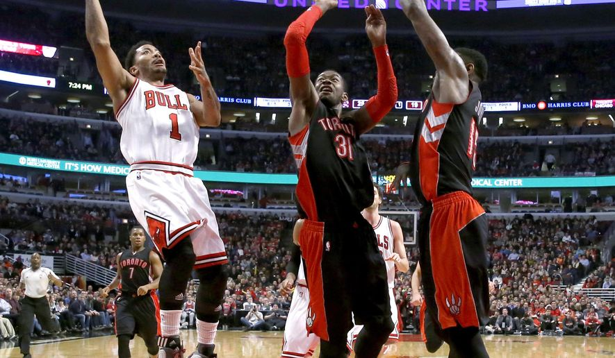 Chicago Bulls guard Derrick Rose (1) shoots as Toronto Raptors' Terrence Ross (31) and Amir Johnson (15) defend during the first half of an NBA basketball game Monday, Dec. 22, 2014, in Chicago. (AP Photo/Charles Rex Arbogast)