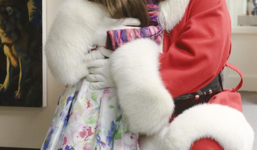 In this Dec. 17, 2014 photo, Corinna Rady, 5, gives Richard Welliver, dressed as Santa Claus, a big hug at North Pole Elementary School in North Pole, Alaska. Welliver, who owns the North Moosed RV Park and Campground in Fox, does volunteer and paid gigs. He spreads holiday cheer at private and public functions in Fairbanks and North Pole throughout the year. (AP Photo/Fairbanks Daily News-Miner, Erin Corneliussen)