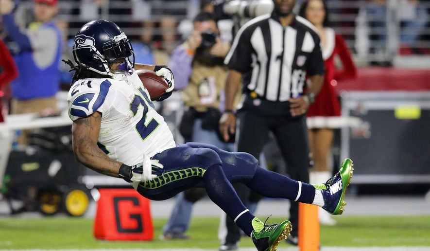 Seattle Seahawks running back Marshawn Lynch leaps into the end zone for a touchdown against the Arizona Cardinals during the second half of an NFL football game, Sunday, Dec. 21, 2014, in Glendale, Ariz. (AP Photo/Rick Scuteri)