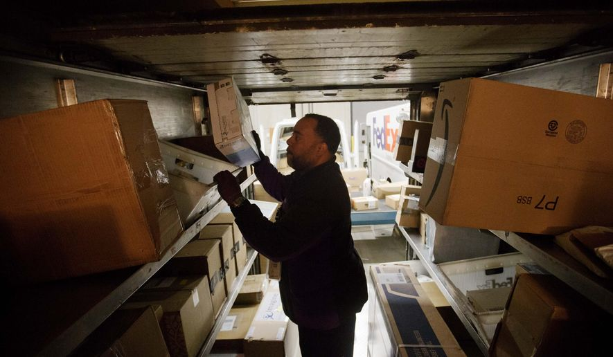 FILE - In this Dec. 15, 2014 file photo, courier Michael Price loads packages onto a truck for delivery at a FedEx facility in Marietta, Ga. FedEx, UPS and e-commerce retailers are trying to avoid the problems that occurred last year when severe winter weather and a surge in late orders caused delivery delays. (AP Photo/David Goldman, File)