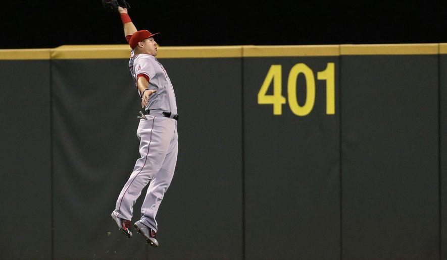 FILE - In this Sept. 26, 2014, file photo, Los Angeles Angels center fielder Mike Trout makes a leaping catch on the run of a ball hit by Seattle Mariners' Kendrys Morales in the eighth inning of a baseball game in Seattle.  (AP Photo/Ted S. Warren)