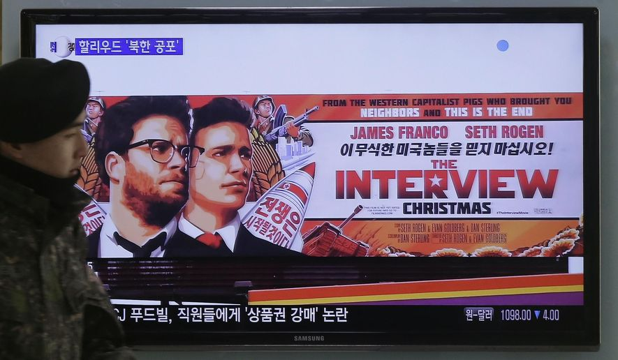 """A South Korean army soldier walks near a TV screen showing an advertisement of Sony Picture's """"The Interview,"""" at the Seoul Railway Station in Seoul, South Korea, Monday, Dec. 22, 2014. North Korea hates the Hollywood film that revolves around the assassination of its beloved leader, but the country has had a long love affair with cinema _ of its own particular styling. (AP Photo/Ahn Young-joon)"""