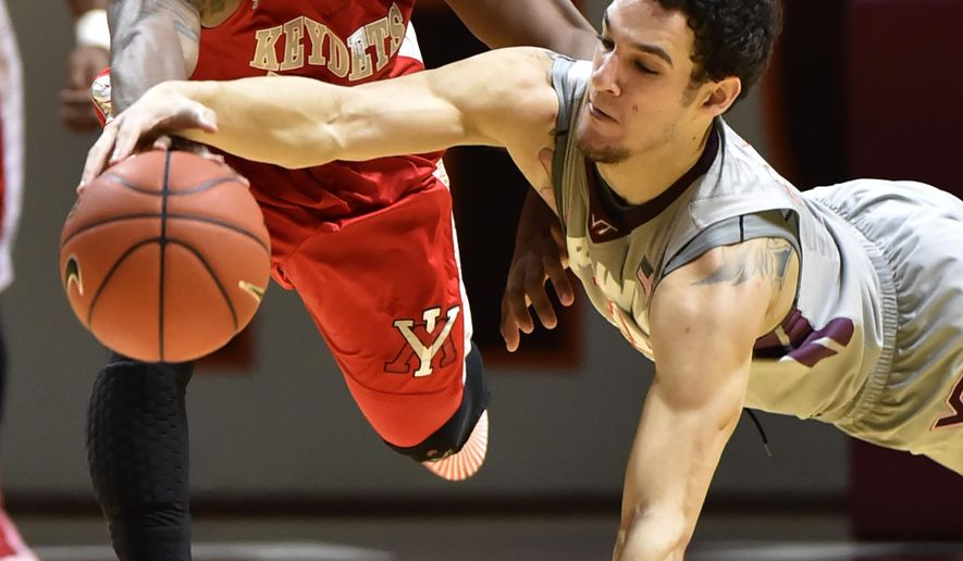 Virginia Tech's Devin Wilson, right, dives for a loose ball VMI's  Q.J. Peterson during the first half of an NCAA college basketball game Monday Dec. 22,  2014, in Blacksburg, Va. (AP Photos-Roanoke Times, Don Petersen)