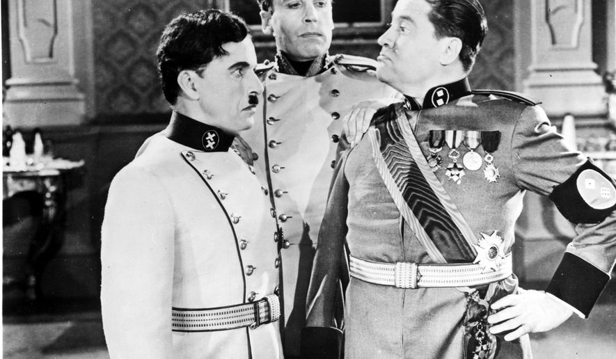 "Confrontation between the Great, Charlie Chaplin, left and Jack Oakie, dictator of bacteria, right, in a scene of the classic satire on Nazi Germany ""The Great Dictator"" from 1940. Henry Daniell as Garbitsch looks on. (AP Photo/HO/Columbia Pictures)"