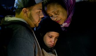 Mourners embrace, Sunday, Dec. 21, 2014, during a vigil near the spot where two New York Police Department officers, sitting inside a patrol car the previous day, were shot by an armed man, killing them both. The assailant then went into a nearby subway station and committed suicide, police said. (AP Photo/Craig Ruttle)