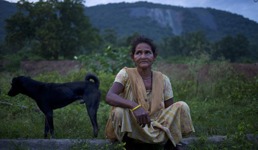 In this Sept. 11, 2014 photo, Jema Sundi sits outside her home in barren hills where asbestos waste was dumped is visible in the background in Roro, India. An asbestos mine, abandoned nearly three decades ago still affects the people around it and 18 along with Jema were diagnosed with asbestosis in 2012. Tens of thousands more, some former mine workers, remain untested and at risk. (AP Photo/Saurabh Das)