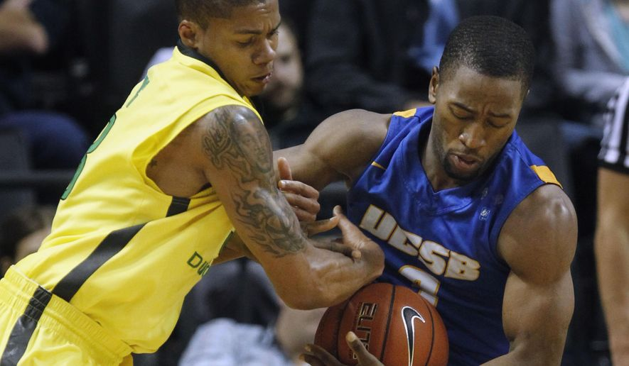 Oregon guard Joseph Young fights for control of the ball with UC Santa Barbara's Zalmico Harmon during the first half of an NCAA college basketball game at Matthew Knight Arena in Eugene, Ore.., on Monday, Dec. 22, 2014. (AP Photo/The Register-Guard, Andy Nelson))