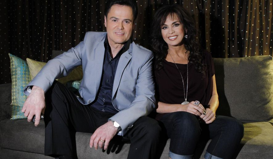 Siblings Donny Osmond, left, and Marie Osmond pose backstage at their show at the Flamingo hotel and casino in Las Vegas in this April 28, 2011, file photo. Donny and Marie Osmond will be singing at the Flamingo Las Vegas at least through the end of 2015. (AP Photo/Isaac Brekken, File)