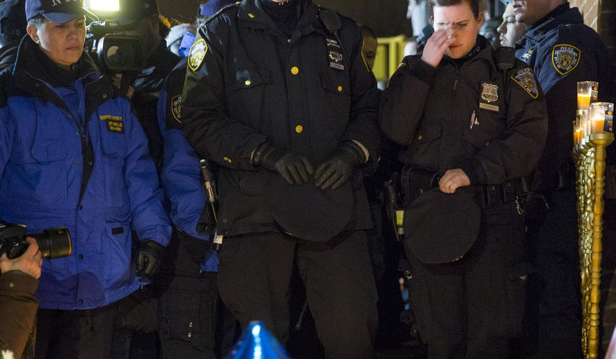 Mourners stand at a memorial Sunday, Dec. 21, 2014, during a vigil near the spot where two New York Police Department officers, sitting inside a patrol car the previous day, were shot by an armed man, killing them both. The assailant then went into a nearby subway station and committed suicide, police said. (AP Photo/Craig Ruttle)