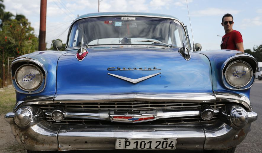 In this Dec. 19, 2014, photo, a man stands beside his 1957 Chevrolet Bel-Air car in Havana, Cuba.  U.S. car sales have been banned in Cuba since 1959. Cubans have been have been forced to patch together Fords, Chevrolets and Chryslers that date back to before Fidel Castro's revolution which can make it appear like the country is stuck in a 1950s time warp. (AP Photo/Desmond Boylan)