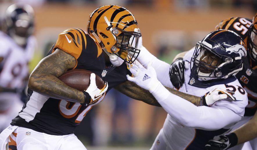 Cincinnati Bengals' Jeremy Hill (32) is tackled by Denver Broncos' Von Miller (58) during the first half of an NFL football game Monday, Dec. 22, 2014, in Cincinnati. (AP Photo/Darron Cummings)