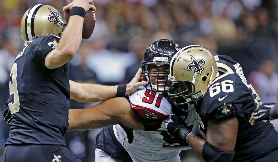 New Orleans Saints quarterback Drew Brees (9) tries to avoid the pass rush of Atlanta Falcons defensive tackle Corey Peters (91) as guard Ben Grubbs (66) defends in the second half of an NFL football game in New Orleans, Sunday, Dec. 21, 2014. (AP Photo/Bill Haber)
