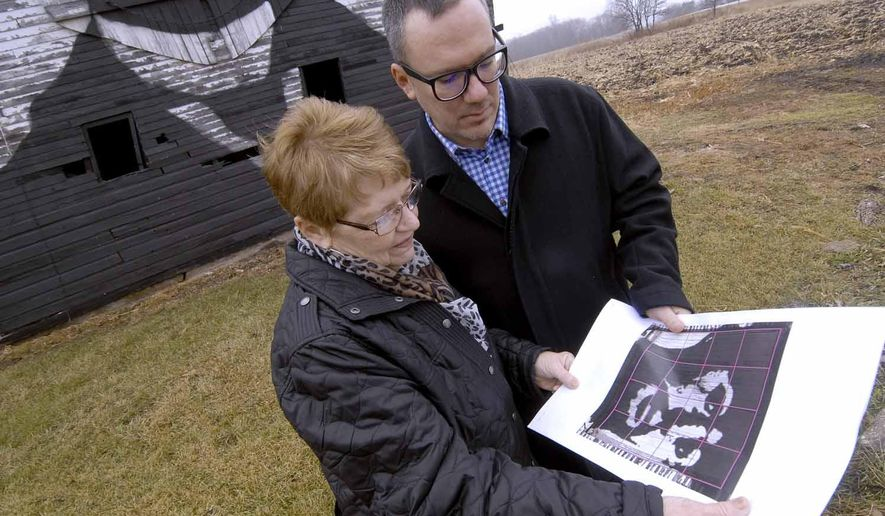 In this Oct. 19, 2014 photo, Jean Peterson, left, of Clive, and her son, Curt Peterson, of Des Moines, look over the grid used to help guide the family as they worked on the portrait of Henri de Toulouse-Lautrec which the family painted on the side of Joan and Ron Peterson's barn, a few miles east of Dayton, Iowa on Iowa Highway 175. Toulouse-Lautrec was a French painter who lived from 1864 to 1901. (AP Photo/The Messenger, Hans Madsen)