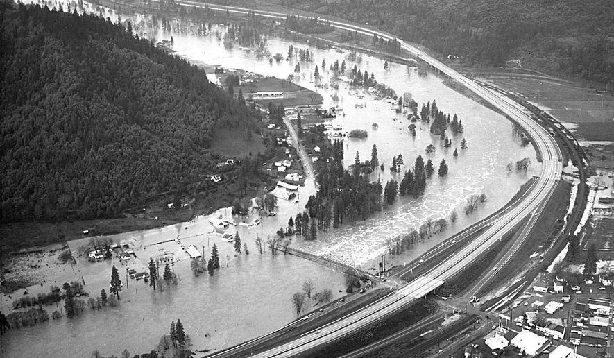 FILE - This Dec. 23, 1964 file photo from the Grants Pass Daily Courier shows the Rogue River flooding the town of Rogue River, Ore. Warm temperatures melting mountain snows combined with heavy rains to push the river out of its banks, cresting at 14 feet above flood stage. (AP Photo/The Grants Pass Daily Courier)