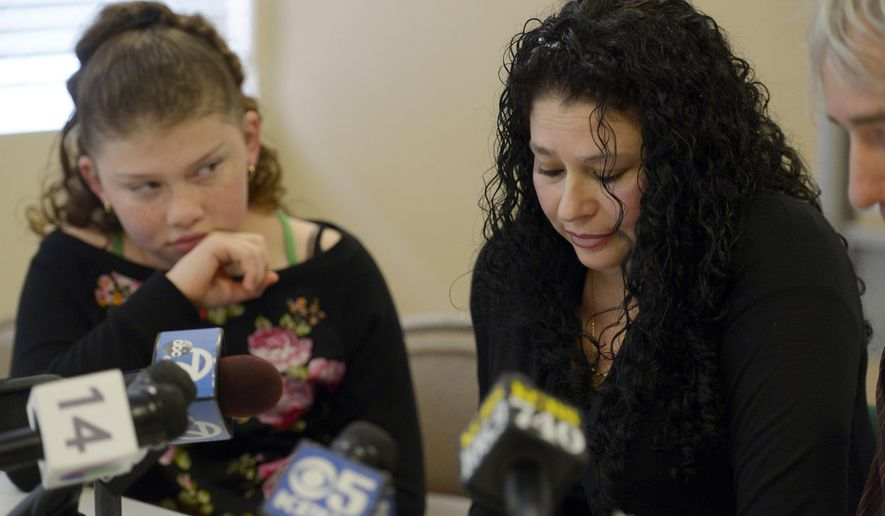 Maricela Perez, 39, of San Leandro, Calif., the wife of a window washer who survived an 11-story fall, lowers her head as her daughter Gaby, 11, listens during a news conference at the SEIU-United Service Workers office Monday, Dec. 22, 2014, in Oakland, Calif. The window washer is expected to soon check into a rehabilitation facility. The family is asking for donations to cover his rehabilitation, rent and other household costs. (AP Photo/Bay Area News Group, Jose Carlos Fajardo) SF BAY AREA PLEASE CREDIT PHOTOGRAPHER AND BAY AREA NEWS GROUP